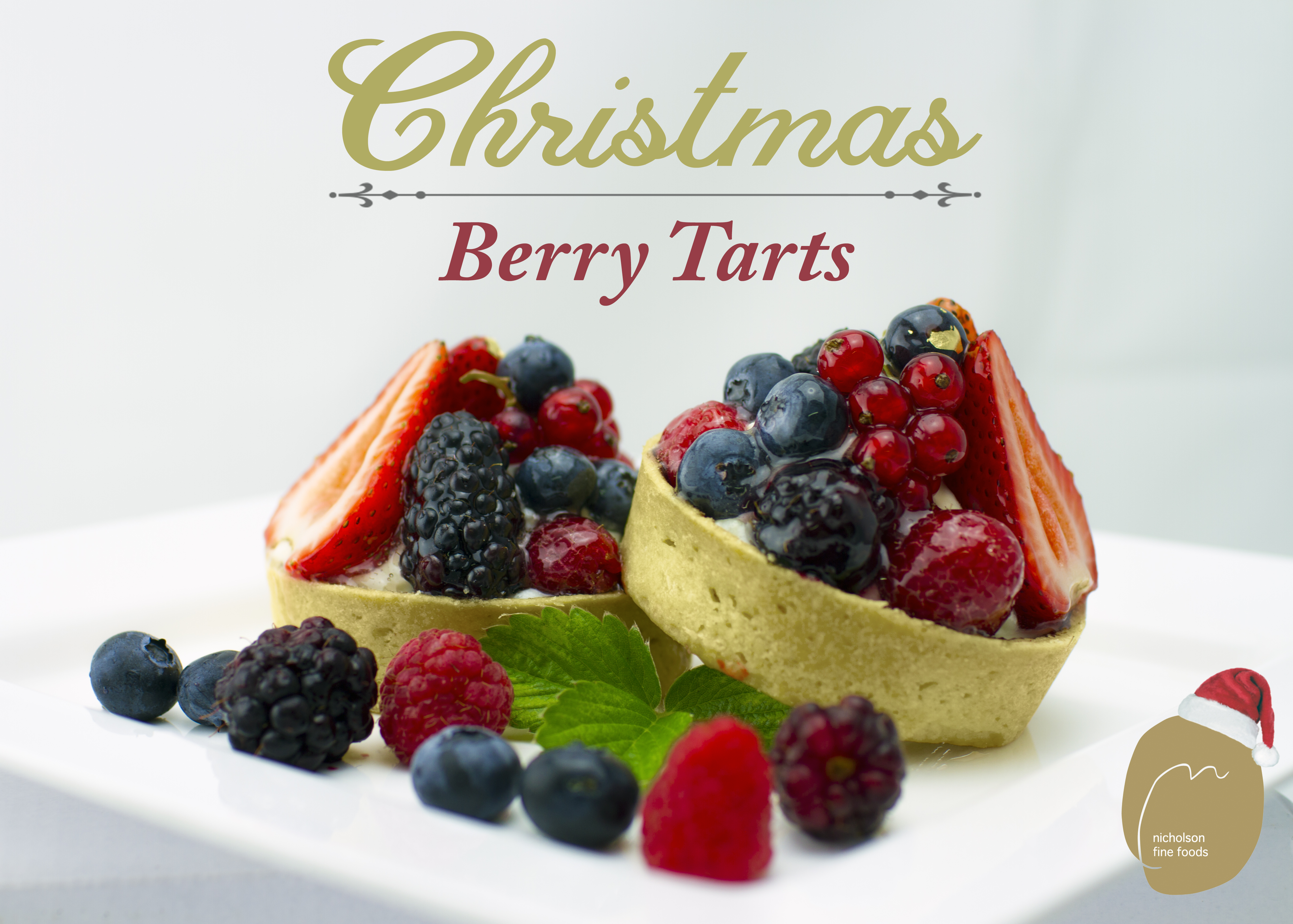 two summer berry Christmas tarts on a plate with mixed berries